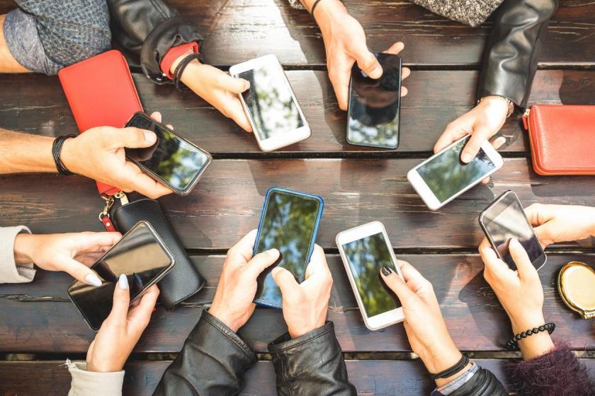 Eine Gruppe von Freunden sitzt mit ihren Smartphones an einem Tisch
