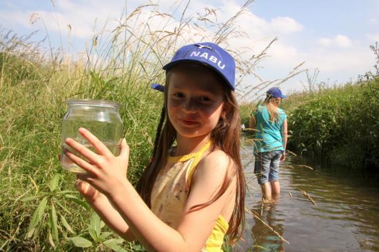 Naturschutz geht uns alle an: Kind bei Naturbeobachtung im Bach